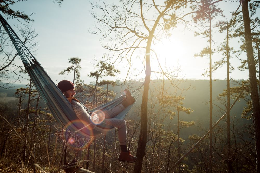 Man relaxing in hammock in rural setting to promote Fatigue management for agency nurses