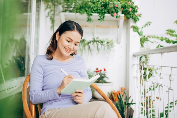 Preparing for your first contract affinity nursing Woman writing in notepad at home